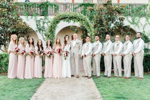 Temecula outdoor wedding at ponte winery bride form fitting lace gown with long sleeves and illusion open back design with sweetheart neckline and groom tan suit with matching vest and white dress shirt with matching tan bow tie and white floral boutonniere with bridesmaids long blush pink dresses with white and red floral bridal bouquets and groomsmen tan suits with matching vests and tan bow ties