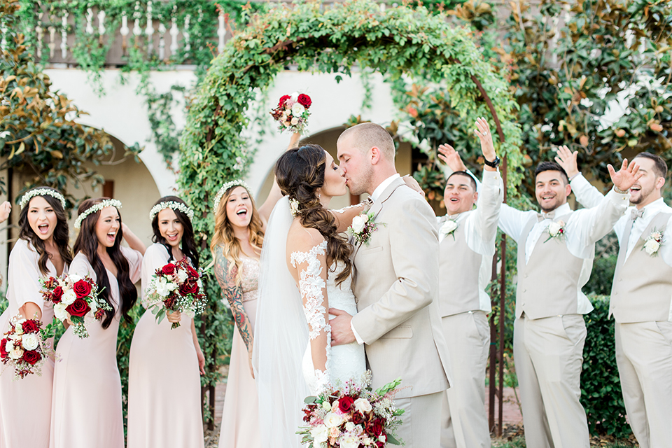 Temecula outdoor wedding at ponte winery bride form fitting lace gown with long sleeves and illusion open back design with sweetheart neckline and groom tan suit with matching vest and white dress shirt with matching tan bow tie and white floral boutonniere kissing with wedding party bridesmaids long blush pink dresses with white and red floral bridal bouquets with groomsmen tan suits with matching vests and tan bow ties