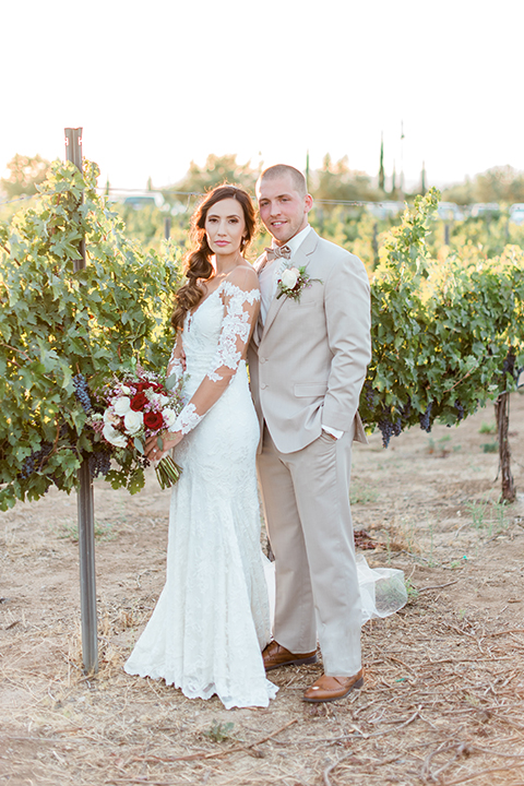 Temecula outdoor wedding at ponte winery bride form fitting lace gown with long sleeves and illusion open back design with sweetheart neckline and groom tan suit with matching vest and white dress shirt with matching tan bow tie and white floral boutonniere bride holding white and red floral bridal bouquet