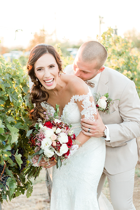 Temecula outdoor wedding at ponte winery bride form fitting lace gown with long sleeves and illusion open back design with sweetheart neckline and groom tan suit with matching vest and white dress shirt with matching tan bow tie and white floral boutonniere laughing bride holding white and red floral bridal bouquet