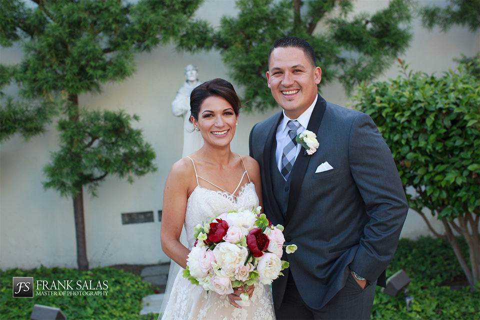 Long beach burgundy wedding at the loft on pine bride ball gown with thin beaded straps and sweetheart neckline with beaded detail on bodice with white and burgundy floral bridal bouquet with groom charcoal grey tuxedo with black shawl lapel and matching vest with white dress shirt and long plaid tie with white pocket square and white floral boutonniere