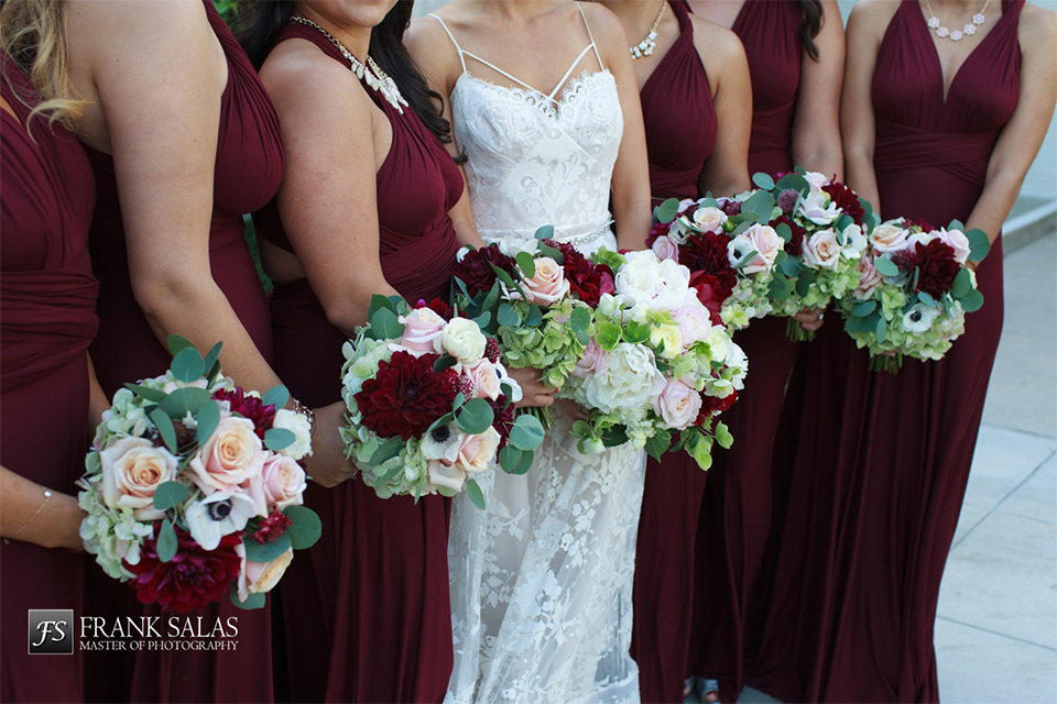 Long beach burgundy wedding at the loft on pine bride ball gown with thin beaded straps and sweetheart neckline with beaded bodice and lace detail with white and burgundy floral bridal bouquet with bridesmaids long burgundy dresses with straps holding white and burgundy floral bouquets