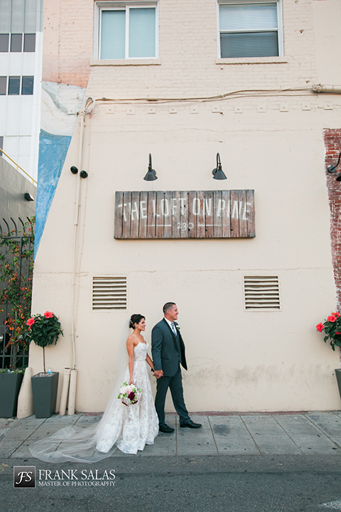 Long beach burgundy wedding at the loft on pine bride ball gown with thin beaded straps and sweetheart neckline with beaded detail on bodice with white and burgundy floral bridal bouquet with groom charcoal grey tuxedo with black shawl lapel and matching vest with white dress shirt and long plaid tie with white pocket square and white floral boutonniere holding hands and walking outside