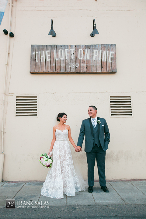 Long beach burgundy wedding at the loft on pine bride ball gown with thin beaded straps and sweetheart neckline with beaded detail on bodice with white and burgundy floral bridal bouquet with groom charcoal grey tuxedo with black shawl lapel and matching vest with white dress shirt and long plaid tie with white pocket square and white floral boutonniere holding hands