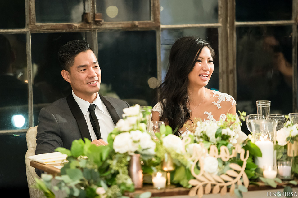 Downtown los angeles wedding bride form fitting lace gown with illusion back and high neckline with crystal hair piece with groom charcoal grey tuxedo with black shawl lapel and white dress shirt with long black skinny tie and white floral boutonniere sitting at table