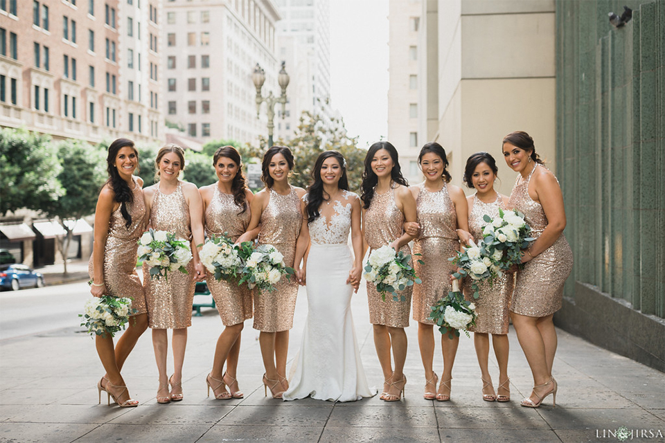Downtown los angeles wedding bride form fitting lace gown with illusion back and high neckline with crystal hair piece with bridesmaids short gold sequined dresses holding white and green floral bridal bouquets