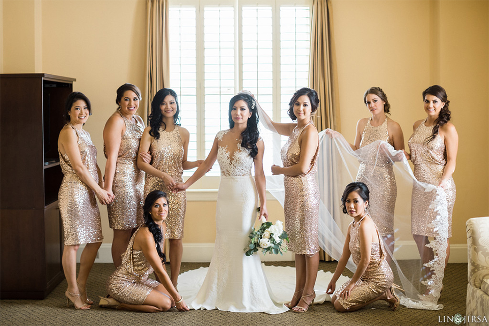 Downtown los angeles wedding bride form fitting lace gown with illusion back and high neckline with crystal hair piece with bridesmaids short gold sequined dresses holding white and green floral bridal bouquets looking at brides dress