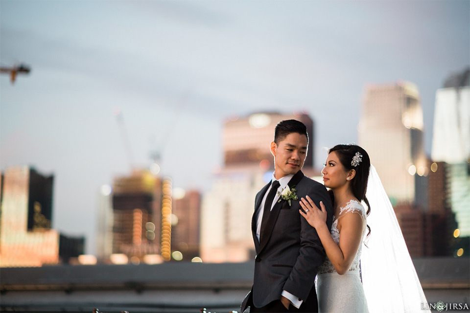 Downtown los angeles wedding bride form fitting lace gown with illusion back and high neckline with crystal hair piece with groom charcoal grey tuxedo with black shawl lapel and white dress shirt with long black skinny tie and white floral boutonniere hugging on rooftop