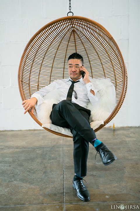 Downtown los angeles wedding groom charcoal grey tuxedo with black shawl lapel and black pants with white dress shirt with long black skinny tie and white floral boutonniere sitting in chair