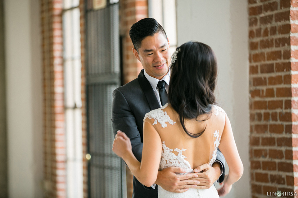 Downtown los angeles wedding bride form fitting lace gown with illusion back and high neckline with crystal hair piece with groom charcoal grey tuxedo with black shawl lapel and white dress shirt with long black skinny tie and white floral boutonniere hugging first look