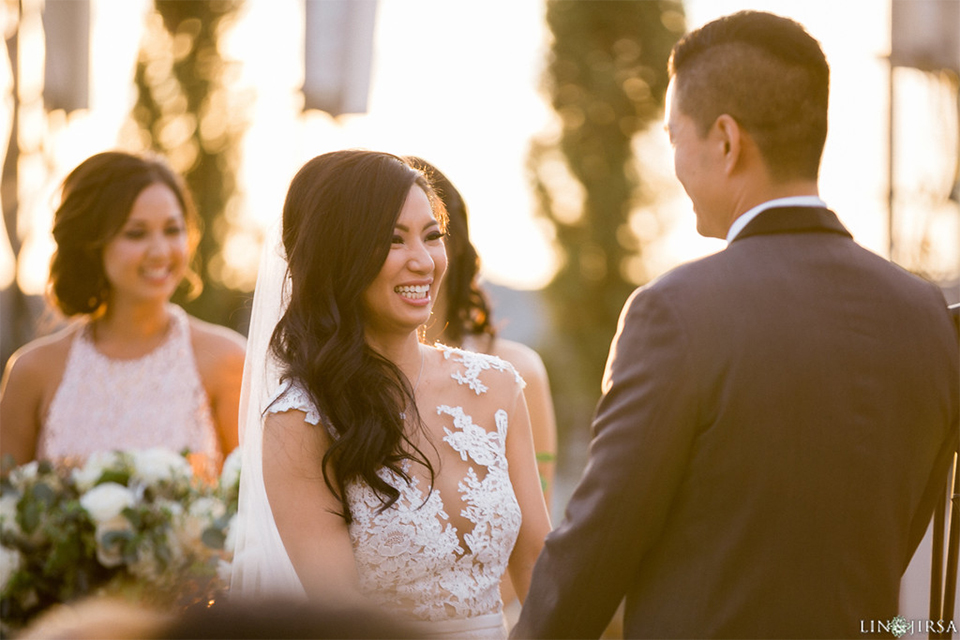Downtown los angeles wedding bride form fitting lace gown with illusion back and high neckline with crystal hair piece with groom charcoal grey tuxedo with black shawl lapel and white dress shirt with long black skinny tie and white floral boutonniere holding hands during ceremony