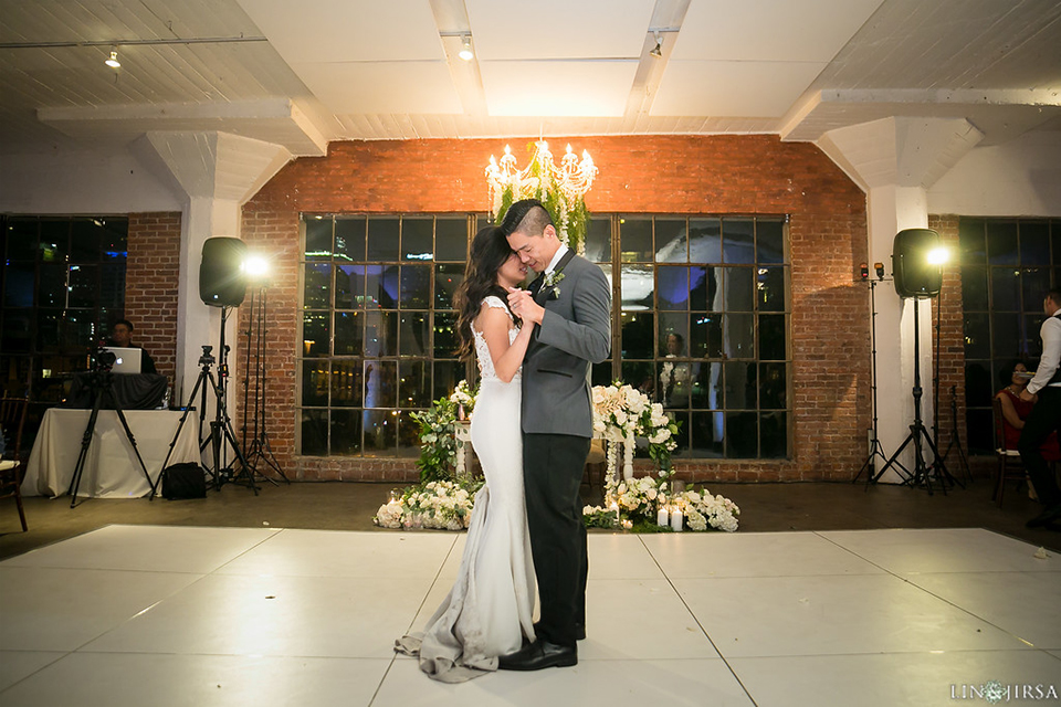 Downtown los angeles wedding bride form fitting lace gown with illusion back and high neckline with crystal hair piece with groom charcoal grey tuxedo with black shawl lapel and white dress shirt with long black skinny tie and white floral boutonniere first dance