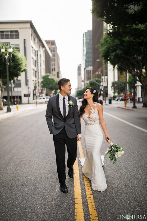 Downtown los angeles wedding bride form fitting lace gown with illusion back and high neckline with crystal hair piece with groom charcoal grey tuxedo with black shawl lapel and white dress shirt with long black skinny tie and white floral boutonniere holding hands and walking in street