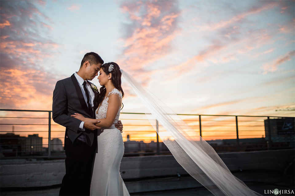 Downtown los angeles wedding bride form fitting lace gown with illusion back and high neckline with crystal hair piece with groom charcoal grey tuxedo with black shawl lapel and white dress shirt with long black skinny tie and white floral boutonniere hugging at sunset