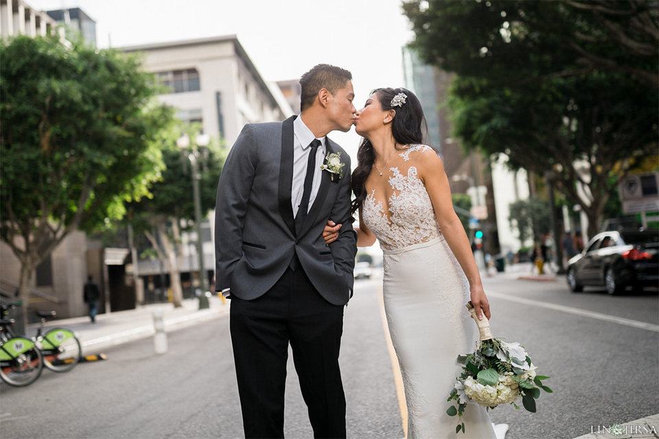 Downtown los angeles wedding bride form fitting lace gown with illusion back and high neckline with crystal hair piece with groom charcoal grey tuxedo with black shawl lapel and white dress shirt with long black skinny tie and white floral boutonniere kissing