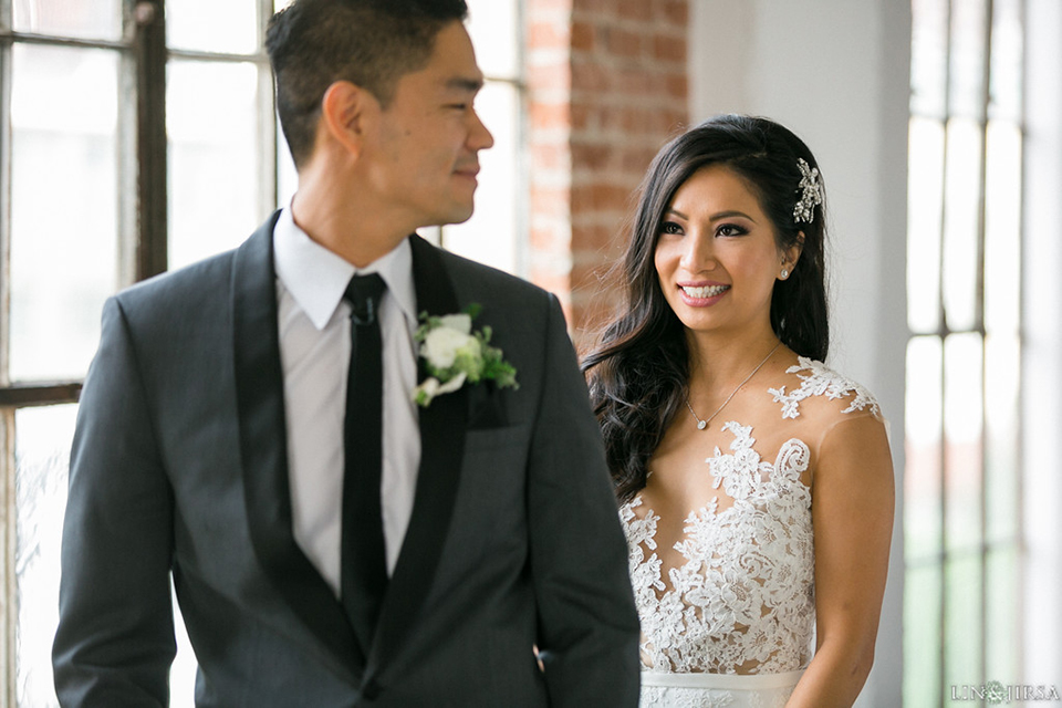 Downtown los angeles wedding bride form fitting lace gown with illusion back and high neckline with crystal hair piece with groom charcoal grey tuxedo with black shawl lapel and white dress shirt with long black skinny tie and white floral boutonniere first look
