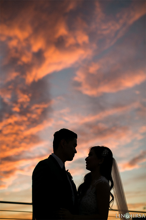 Downtown los angeles wedding bride form fitting lace gown with illusion back and high neckline with crystal hair piece with groom charcoal grey tuxedo with black shawl lapel and white dress shirt with long black skinny tie and white floral boutonniere at sunset