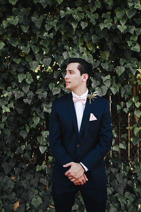 Orange county outdoor rustic wedding at the riverbed farm groom navy blue notch lapel suit with white dress shirt and blush pink bow tie with matching pocket square and white and green floral boutonniere standing with hands crossed