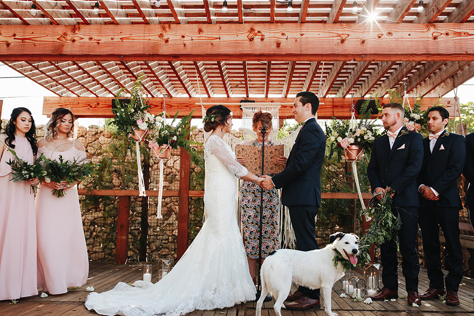 Orange county outdoor rustic wedding bride form fitting lace gown with sleeves and plunging neckline with groom navy blue notch lapel suit with white dress shirt and blush pink bow tie with matching pocket square and whit and green floral boutonniere holding hands during ceremony