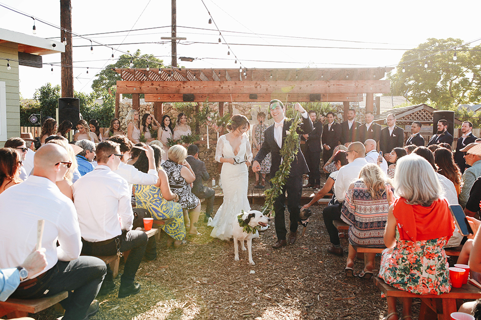Orange county outdoor rustic wedding bride form fitting lace gown with sleeves and plunging neckline with groom navy blue notch lapel suit with white dress shirt and blush pink bow tie with matching pocket square and whit and green floral boutonniere walking down the aisle after ceremony with dogs