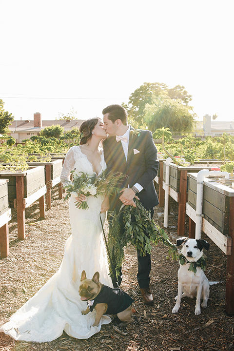 Orange county outdoor rustic wedding bride form fitting lace gown with sleeves and plunging neckline with groom navy blue notch lapel suit with white dress shirt and blush pink bow tie with matching pocket square and whit and green floral boutonniere kissing