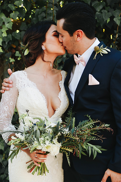 Orange county outdoor rustic wedding bride form fitting lace gown with sleeves and plunging neckline with groom navy blue notch lapel suit with white dress shirt and blush pink bow tie with matching pocket square and whit and green floral boutonniere kissing bride holding green and white floral bridal bouquet