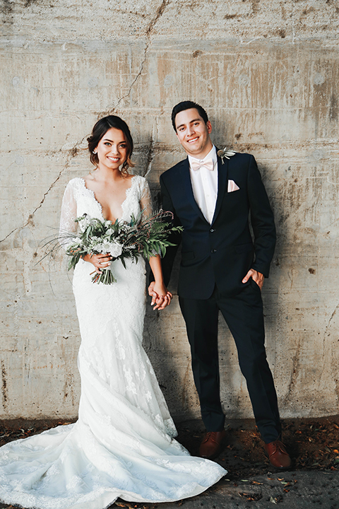 Orange county outdoor rustic wedding bride form fitting lace gown with sleeves and plunging neckline with groom navy blue notch lapel suit with white dress shirt and blush pink bow tie with matching pocket square and whit and green floral boutonniere holding hands and bride holding green and white floral bridal bouquet