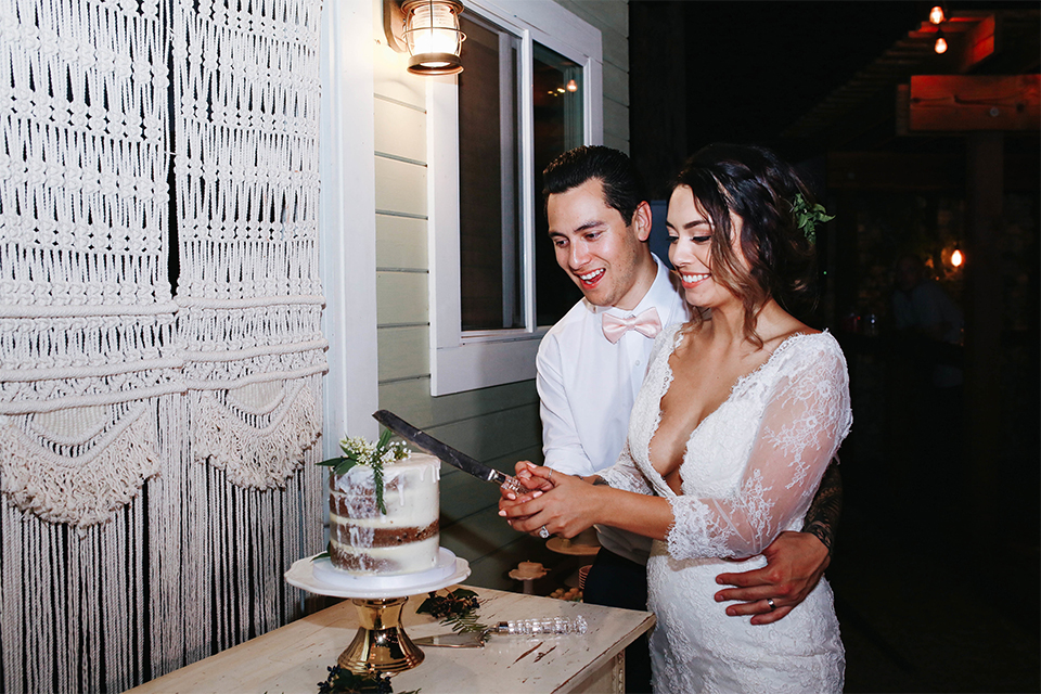 Orange county outdoor rustic wedding bride form fitting lace gown with sleeves and plunging neckline with groom navy blue notch lapel suit with white dress shirt and blush pink bow tie with matching pocket square and whit and green floral boutonniere cutting cake