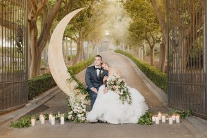 California wedding shoot at enchanted forest bride ball gown with high illusion neckline and lace sleeves with ruffled skirt and open back design with groom navy blue shawl lapel tuxedo with matching vest and white dress shirt with black bow tie and white floral boutonniere sitting on crescent moon decor with flowers and candles on ground bride holding white and green floral bridal bouquet
