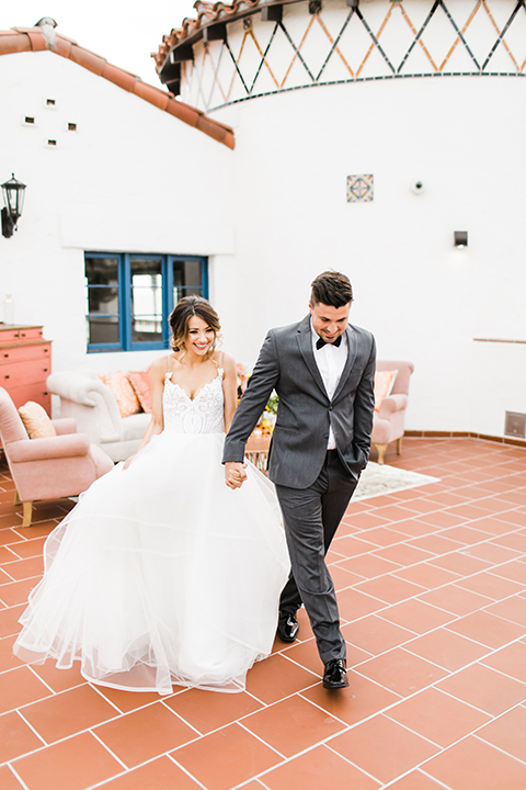 Orange county beach wedding at ole hanson beach club bride ball gown with thin straps and sweetheart neckline with low back design and lace details with groom charcoal grey tuxedo with white dress shirt and black bow tie holding hands and walking