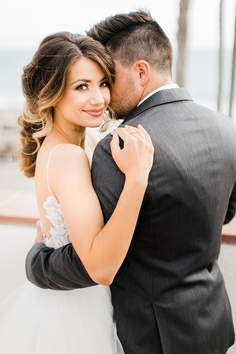 Orange county beach wedding at ole hanson beach club bride ball gown with thin straps and sweetheart neckline with low back design and lace details with groom charcoal grey tuxedo with white dress shirt and black bow tie hugging close up