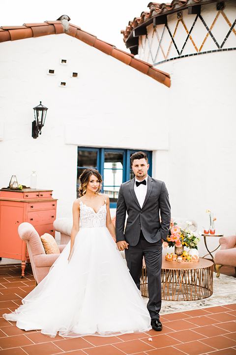 Orange county beach wedding at ole hanson beach club bride ball gown with thin straps and sweetheart neckline with low back design and lace details with groom charcoal grey tuxedo with white dress shirt and black bow tie standing by lounge furniture holding hands