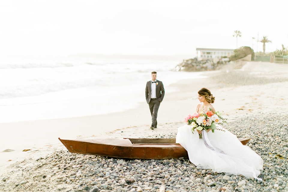 Orange county beach wedding at ole hanson beach club bride ball gown with thin straps and sweetheart neckline with low back design and lace details with groom charcoal grey tuxedo with white dress shirt and black bow tie bride sitting in boat with groom walking