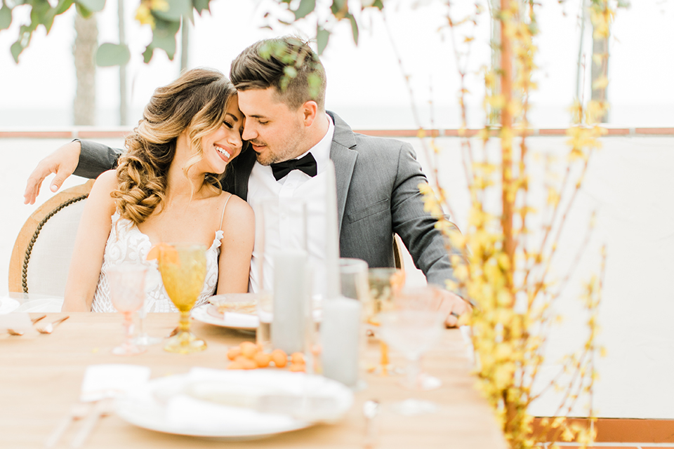 Orange county beach wedding at ole hanson beach club bride ball gown with thin straps and sweetheart neckline with low back design and lace details with groom charcoal grey tuxedo with white dress shirt and black bow tie sitting at table hugging and smiling