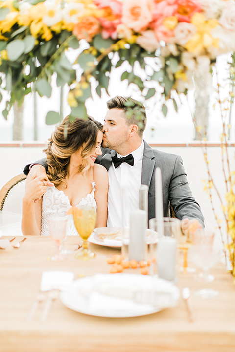 Orange county beach wedding at ole hanson beach club bride ball gown with thin straps and sweetheart neckline with low back design and lace details with groom charcoal grey tuxedo with white dress shirt and black bow tie sitting at table hugging