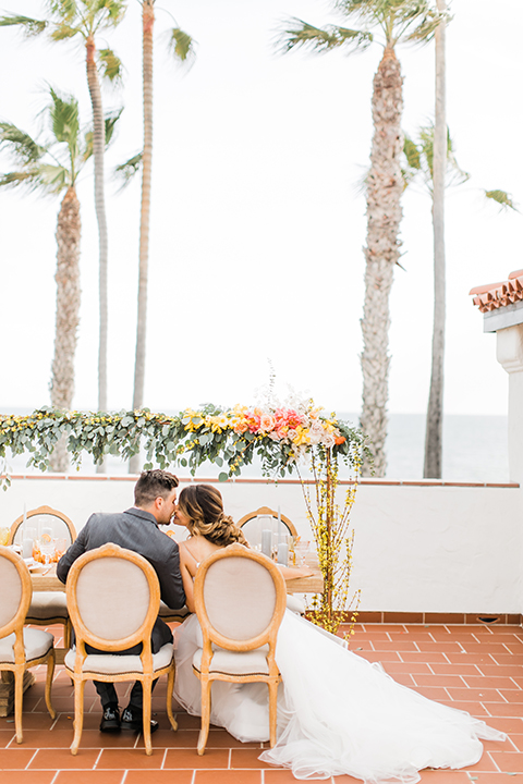 Orange county beach wedding at ole hanson beach club bride ball gown with thin straps and sweetheart neckline with low back design and lace details with groom charcoal grey tuxedo with white dress shirt and black bow tie sitting at table kissing