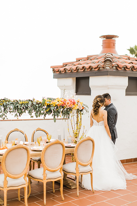 Orange county beach wedding at ole hanson beach club bride ball gown with thin straps and sweetheart neckline with low back design and lace details with groom charcoal grey tuxedo with white dress shirt and black bow tie standing by table holding hands