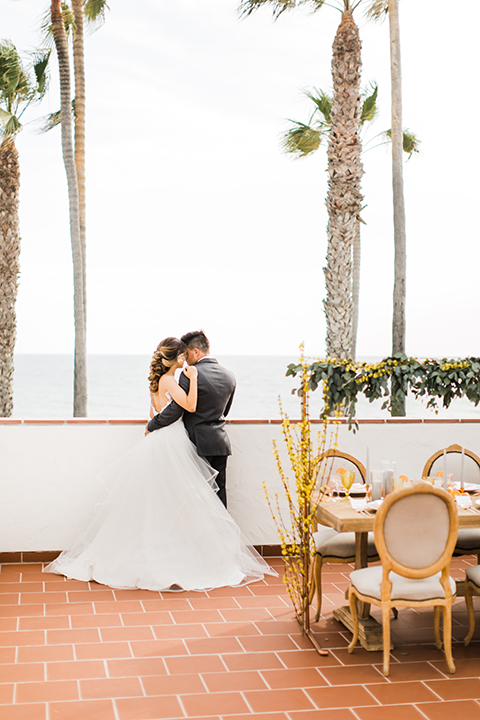 Orange county beach wedding at ole hanson beach club bride ball gown with thin straps and sweetheart neckline with low back design and lace details with groom charcoal grey tuxedo with white dress shirt and black bow tie standing by table hugging