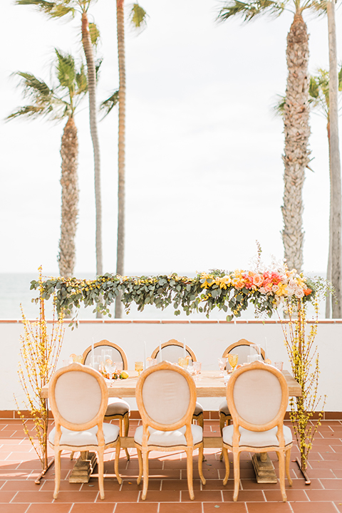 Orange county beach wedding at ole hanson beach club table set up light brown wood table with pink and white flower decor with oranges and fruit decor with white and brown chairs and white polka dot place settings with calligraphy place cards and hanging greenery floral decor