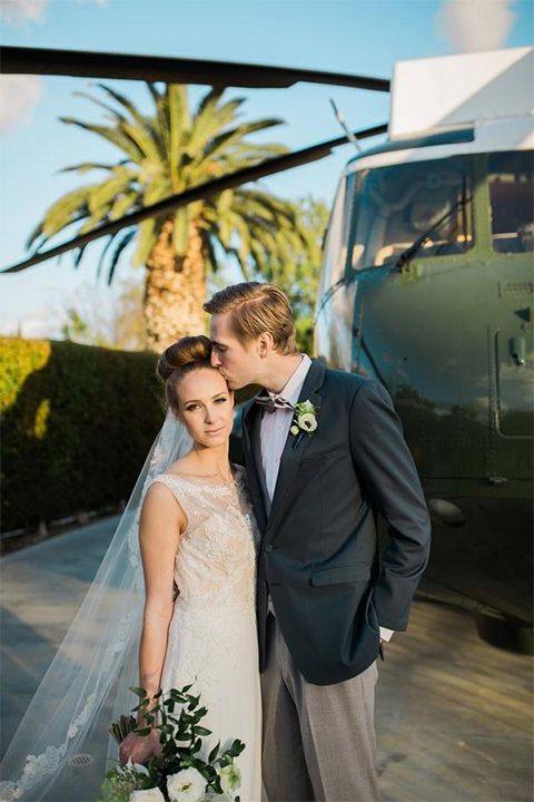 Orange county nautical navy wedding at the nixon library bride chiffon gown with lace bodice and high neckline with hair in bun and long veil with groom slate blue coat with heather grey pants and matching vest with white dress shirt and heather grey pipe edge bow tie and white floral boutonniere standing by helicopter hugging and kissing bride holding white and green floral bridal bouquet