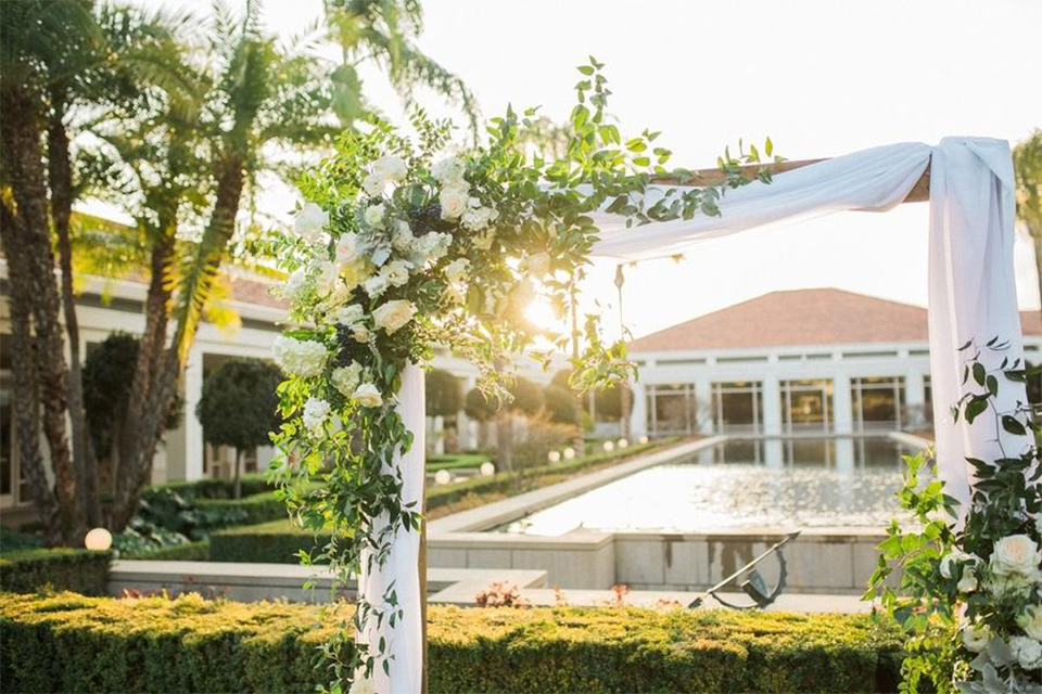 Orange county nautical navy wedding at the nixon library ceremony set up on grass with blue chairs and wood arch with white chiffon decor and white and green flower decor on top and on side overlooking water and venue in background wedding photo idea for ceremony set up