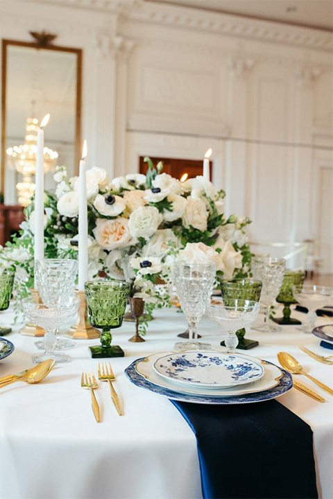 Orange county nautical navy wedding at nixon library table set up with white table linen and green and white flower decor with gold candle lanterns on floor with navy blue suede chairs and tall white candle decor with white and blue place settings and gold silverware