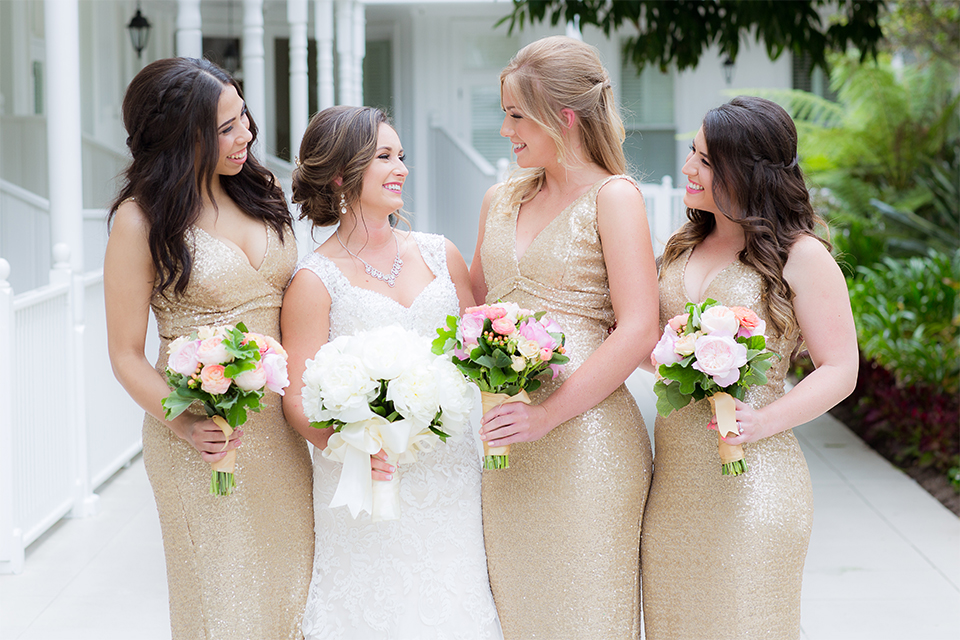 San diego wedding at the crossings carlsbad bride form fitting lace gown with thin straps and ruffled skirt with sweetheart neckline holding white floral bridal bouquet with bridesmaids long gold sequined dresses with high necklines and white and pink floral bridal bouquets