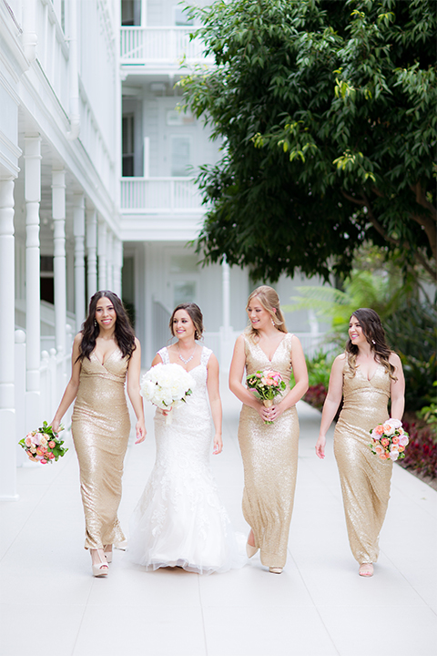 San diego wedding at the crossings carlsbad bride form fitting lace gown with thin straps and ruffled skirt with sweetheart neckline holding white floral bridal bouquet with bridesmaids long gold sequined dresses with high necklines and white and pink floral bridal bouquets walking