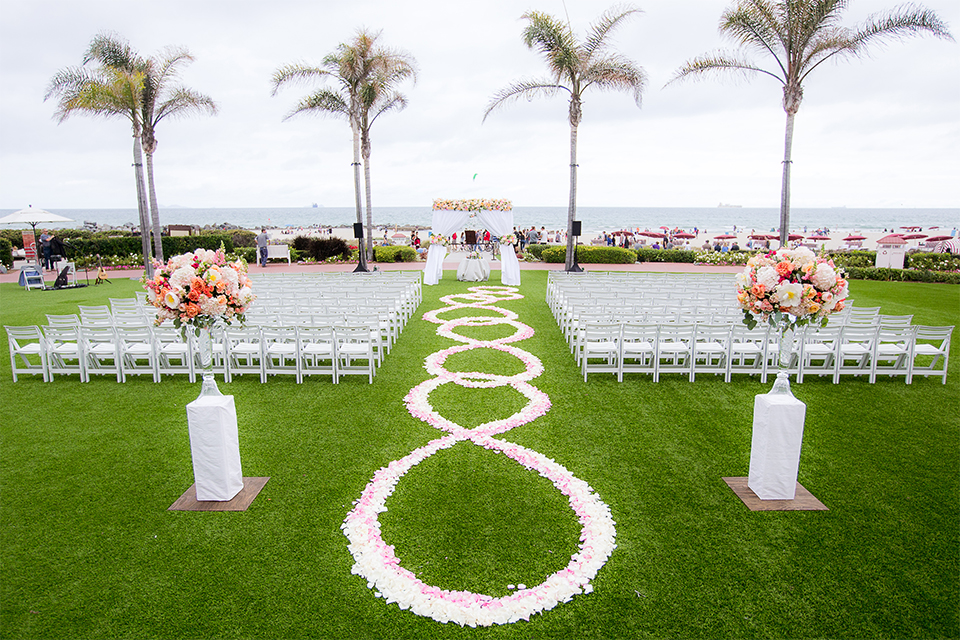 San diego wedding at the crossings carlsbad ceremony set up with white chairs and white and pink flower petals decor along middle of the aisle with palm trees in background and white chiffon on altar wedding photo idea for ceremony