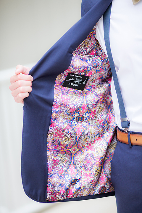 San diego wedding at the crossings carlsbad groom cobalt blue suit with white dress shirt and gold bow tie with matching pocket square and white floral boutonniere with pink paisley design on inside of jacket with blue suspenders and brown belt