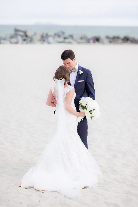 San diego wedding at the crossings carlsbad bride form fitting lace gown with thin straps and ruffled skirt with sweetheart neckline and long veil with groom cobalt blue suit with white dress shirt and gold bow tie with matching pocket square and white floral boutonniere hugging on the beach bride holding white floral bridal bouquet