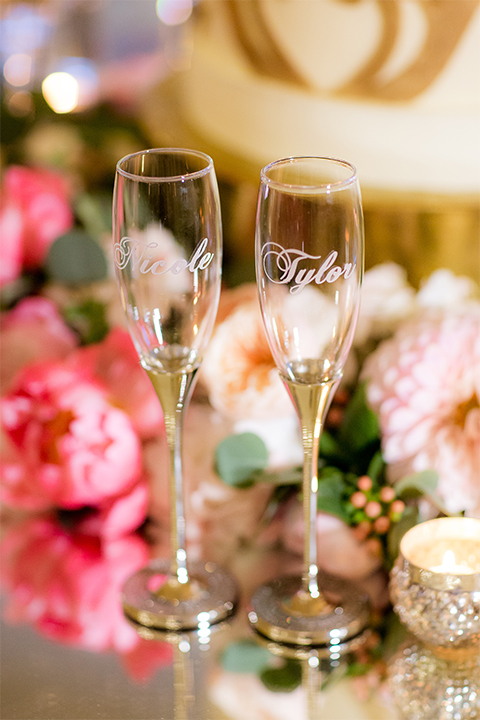 San diego wedding at the crossings carlsbad table set up with white table linen and gold chairs with white and pink flower centerpiece decor with white place settings and candle decor with blue and gold table numbers with bride and groom champagne flutes for toast