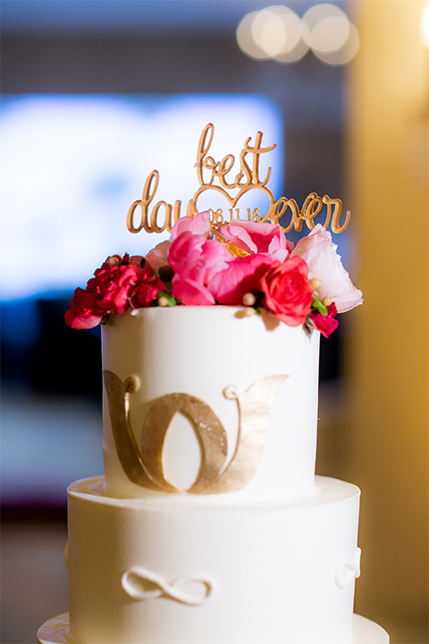 San diego wedding at the crossings carlsbad two tier white wedding cake with gold decor and gold calligraphy cake topper with white and pink flower decor on top wedding photo idea for cake