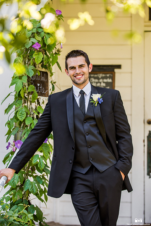 San diego wedding at green gables estate groom black shawl lapel tuxedo with matching vest and white dress shirt with long black skinny tie and white floral boutonniere